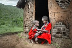 Africa | Two Masai boys outside a hut in their village in Kenya. The colour red is worn to represent power, and accessories and body ornaments are be worn to reflect their identity and status in society. | © David Lazar