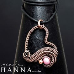 This asymmetrical wire wrap heart pendant features a lovely focal pink freshwater pearl bead with and accent copper bead. The copper wire has been hand woven and layered to emphasize the texture of the weaves and the depth of the design. Pendant, measuring 3cm in length, will arrive with 18 black rub