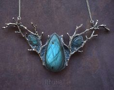 Elaborate labradorite necklace in a shape of copper branches embracing golden-green stone that reminds of will-o-the-wisps and faerie lights. A tiny wearable fairy tale to adorn your neck and bring a bit of very special magic to your everyday look. Far in the wilderness, the lights are dancing in small circles on a moonless night. Its a sight to behold, but the true beauty of the dance can only be seen from above. If one were to fly up in the sky and look down upon the marshes, they would…