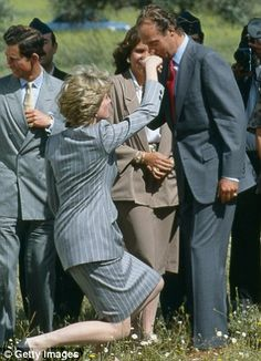 Princess Diana curtseys to King Juan Carlos of Spain, who kisses her hand, as she and Prince...