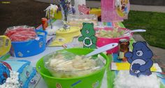 Care Bear Table Set Tubs are from dollar store with dollar store stickers, Rainbow table cloth, and hand made Care Bears each bowl has a different fruit on popsicle sticks for easy eating