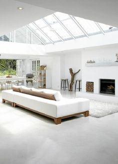 Low level furniture, white, wood and natural decor flooded with light! .. Just needs some plants
