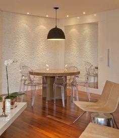 As cadeiras em acrílico transparente utilizadas pela designer de interiores Patricia Pasquini contrastam de forma elegante com a parede em relevo e o moderno lustre preto.