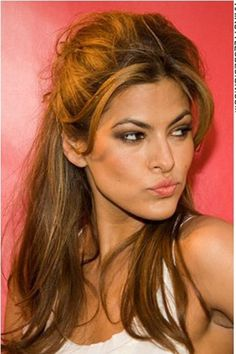 """For this hairstyle, Eva Mendes has her hair long and thick. The hair from the sides has been pulled up and styled towards the back with a hair clip. Long bangs have been left loose on the front at the forehead. This rockabilly style is chic and fun.<span id=""""desc_split""""></span>Eva's haircut is long.<span id=""""desc_split""""></span>Her hair colour is a rich and healthy looking light brown."""