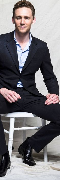 Tom Hiddleston sitting as only Tom Hiddleston can, and still look like a gentleman. I've figured it out. They  keep giving him these low chairs, and his legs are a mile long. What the heck else is he supposed to do?