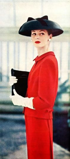 """The bow-back jacket with the slim paneled skirt in clear red wool by Arthur Jablow, worn with a black leghorn hat by Sally Victor, patent-leather envelope bag by Greta."" Ladies Home Journal, March, 1956"