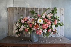 Bouquet includes: 'Coral Charm' peonies, rose 'Ghislaine de Feligonde' and 'Dupontii', apples, sweet peas, foxglove, wild roses, ninebark foliage.