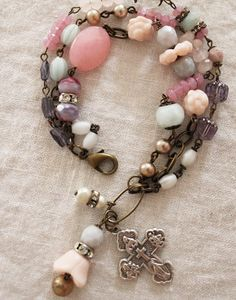 Beads include pale pink vintage Czech glass flower beads, vintage pearls, faceted Iolite stones, an oversized pink Jade oval bead, round faceted Czech glass beads, Rose Quartz stones, vintage Mother of Pearl rosary beads, a vintage 4-way cross medal and a bit of sparkle from old rhinestone rondelles.