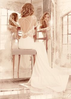 Style 6559 Mona / Ivory long sleeve lace sheath bridal gown, illusion bateau neckline with V-front and keyhole back, piping detail and sheer lace accent at hip, slim silk crepe skirt.