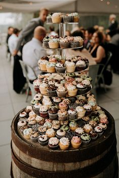 What a great idea for wedding cupcakes! This display of mini cupcakes on a tiered stand atop a rustic barrel is a fun display. A great alternative to wedding cake. By Kim Jay Weddings Fall Wedding Cupcakes, Wedding Cake Stands, Cupcake Stands For Weddings, Wedding Cupcakes Display, Rustic Cupcake Display, Wedding Cake And Cupcake Stand, Cupcakes Fall, Rustic Wedding Desserts, Rustic Cupcake Stands