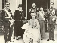 Queen Marie of Romania holding her grandson,Peter at his christening in her is King Ferdinand of Romania.To the right are the Duke and Duchess of York.To her left are the King and Queen of Yugoslavia. Duchess Of York, Duke Of York, Duke And Duchess, Queen Mary, Queen Elizabeth, Queen Mother, King Alexander, Christening Photos, Young Prince