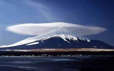 Mt Fuji with a hat.  This is an example of a lenticular cloud, also known as altocumulus standing lenticularis. These are stationary, lens-shaped clouds that are formed at high altitudes. They are included in the middle layer cloud family because the bases of the clouds are stationed between about 2,000 and 7,000 meters. These clouds form when moist air is forced to flow up around mountains and large hills. The water is super cooled and condensed from air below the dew point temperature.