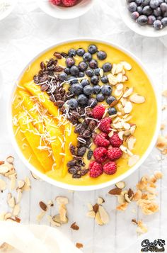 Kick start your day with this delicious and healthy Mango Smoothie Bowl topped with raisins, berries, shredded coconut and sliced almonds! It is also vegan. #breakfast #healthy #vegan