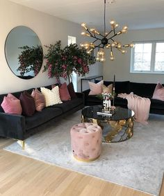 light black sofa with dusty pink cushion shades completing the look with gold chandelier and gold coffee table