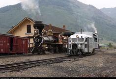 "As part of the DSNG ""Railfest"" activities, Eureka  Palisade 4, 4-4-0 (BLW 3763 / 1875), a wood-burner, simmers at the DSNG Silverton, Colorado depot as Rio Grande Southern 5, a ""Galloping Goose,"" prepares to depart."