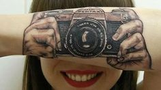 A Dutch tattoo artist has created an incredible optical illusion artwork on her daughter's forearm that makes it look like she's taking a photograph. Brunssum-based tattoo artist Helma van der Weide's tattoo for her daughter Lotte van den Acker shows a vintage 1970s Ashahi Pentax 35mm SLR, an iconic design that influenced generations of cameras.