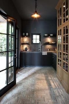 Summer style!! Black kitchen - even the ceiling is painted black! - with faded brick floor!! Look at the gorgeous pale wood kitchen cabinet on the right!