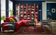 Salon, rouge et bleu avec le canapé KIVIK 3 places confortable avec chaise longue rouge installé près de la fenêtre.