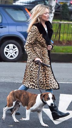Kate Moss wears jeans, black riding boots, a leopard print coat