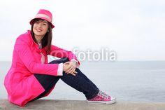 Ragazza sorridente seduta sul muretto