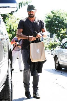 Hollywood hunk: Colin wore a khaki cap with leather jacket , T-shirt, grey fitted jeans and leather boots