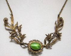 Vintage Art Deco filigree flower necklace Green glass oval cabochon Interwoven leaves and flowers in the centerpiece, attached to a rope chain Gold tone, shows wear only on the clasp Clasp and end ring are stamped with a D 19 inches long Very good vintage condition, nicely detailed I specialize in Art Deco jewelry, please visit my store   International buyers welcome, over charges are refunded Priority shipping options are offered  Want to see more great necklaces? Click here: https:/&#x...