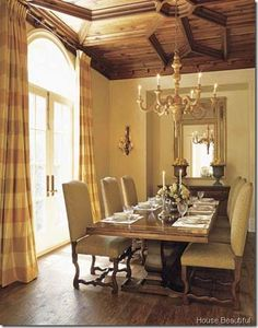Walnut coffered ceiling over french trestle table with ceiling height plaid curtains
