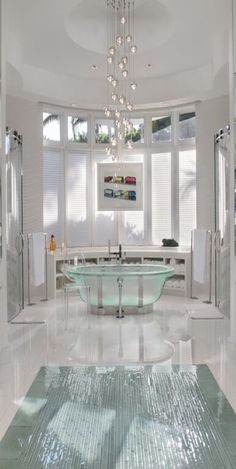 A modern bathroom with mosaic tile, an opaque soaking tub, and large windows. hanging from the soaring ceiling is a bubble chandelier in metallics.