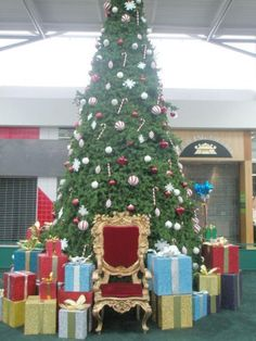 I like the big wrapped boxes around Santa's chair. Maybe get families to donate a box and some wrapping for décor.