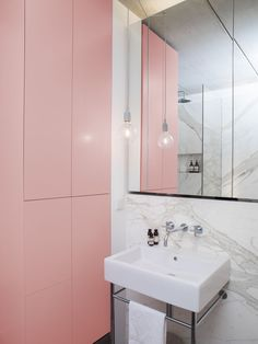A tiny bathroom with pink cabinets and a marble wall