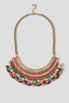 The Jaylynn Statement Necklace is here right in time for music festival season! The Boho bib necklace features a cascading variety of elements to it. To start is a textured gold plate adorned with garnet stones with a thick strand of woven pink & white thread attached to a gold chain that is adorned with multi-color stones & beads then lastly finished with a braided seed bead strand. The end result is a unique & fun necklace!