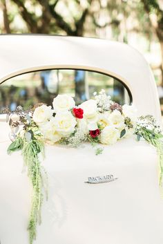 Beautiful florals on a vintage Packard. Vintage car from Timeless Motorcoaches, florals by Gray Harper Event Maker, image by Simply Sarah Photography. #wedding