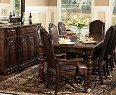 """Normandie Manor Dining  $2649  The smooth rectangular table top has a beveled edge and a distinctive crossing pattern with rich contrasting pine and walnut veneers. The table also has two 18"""" leaves. The arm chairs have high backs and a rich wood frame."""