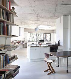 Dom architektki Małgorzaty Sadowskiej i malarza Marka Sobczyka schowany jest w podwarszawskim lesie. Z zewnątrz okrywają go deski w naturalnym kolorze, które powtarzają rytm sąsiadujących z nim drzew. Wewnątrz jest bardziej surowo – beton, żywica epoksydowa i duże przeszklenia to tło dla minimalistycznego wystroju oraz mebli zaprojektowanych przez właścicieli.