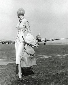 A woman looks back on her plane. Another successful landing in a stylish suit.