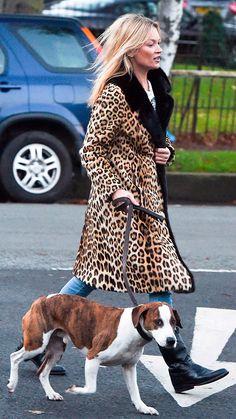 Street style look de Kate Moss usando casaco longo animal print onça com calça jeans e bota.