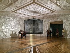 "ArtPrize visitors in the gallery with Anila Quayyum Agha's ""Intersections"" at the Grand Rapids Art Museum"