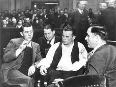 John Dillinger surrounded by guards at his arraignment in Crown Point, Indiana on the charge of killing a policeman. Feb 9, 1934.