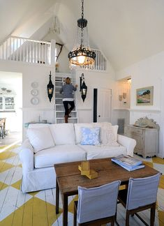 Storybrook Cottage in Leipers Fork, TN. Love the chevron floors with linen furniture and lanterns flanking stairs to a quaint loft.