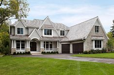 Stunning traditional home exterior. Cape Cod Style. Stone and shaker shingle siding. Gray and beige, all very neutral. Dark contrasting garage door and front door. Large front porch with columns.