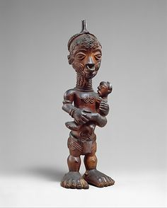 Maternity Figure (Bwanga bwa Cibola)  Date:     19th–early 20th century Geography:     Democratic Republic of the Congo Culture:     Luluwa peoples Medium:     Wood, metal ring Dimensions:     H. 9 3/4 x W. 3 x D. 2 1/2 in. (24.8 x 7.6 x 6.4 cm) Classification:     Wood-Sculpture