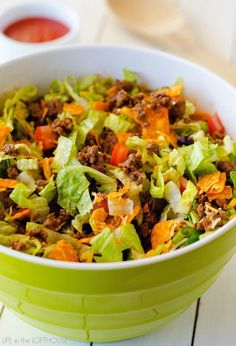 Doritos Taco Salad - Life In The Lofthouse 1 pound lean ground beef 1 packet (1.25 oz) taco seasoning 2 Romaine lettuce hearts, rinsed then chopped 1 cup black beans, rinsed 1 large tomato, seeded then chopped 1/2 cup shredded cheddar cheese 1 cup nacho cheese Doritos, broke into bite size pieces 1 cup Catalina dressing