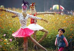 "Little girl playing around ""dancing"" scarecrows in Gulin Park, Nanjing, China."