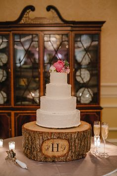 white wedding cake with floral topper on wood stump
