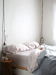 warm modern bedroom with pastel bedding and hanging pendant lamps