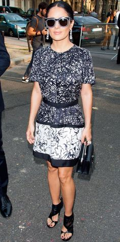Look of the Day › September 26, 2013 WHAT SHE WORE Hayek sat front row at the Balenciaga spring/summer 2014 show in Paris in belted graffiti-like black-and-white graphic print dress, styling it contrasting shades, drop earrings, satin black bag and open-toed booties.