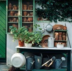 Potting bench with lots of pots and watering cans