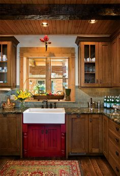 In the kitchen, an apron-front farm sink rests on a red-stained cabinet, contrasting with the oak cabinets and green granite countertops.