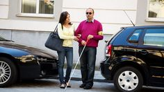 A woman helping a man that is visually impaired cross the street. :) help some one today