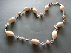 Collana con elementi in resina di tre gradazioni di colore e perle, montata con componenti in metallo color argento. Realizzazione artigianale.